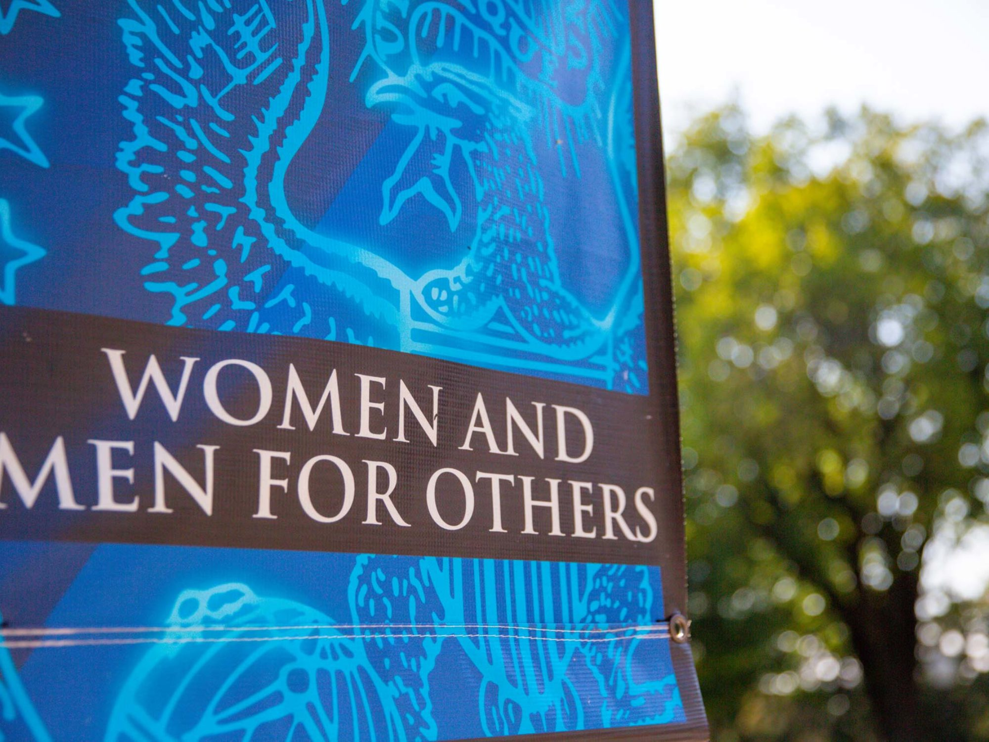 Banner hanging on campus lamppost that reads Women and Men for Others