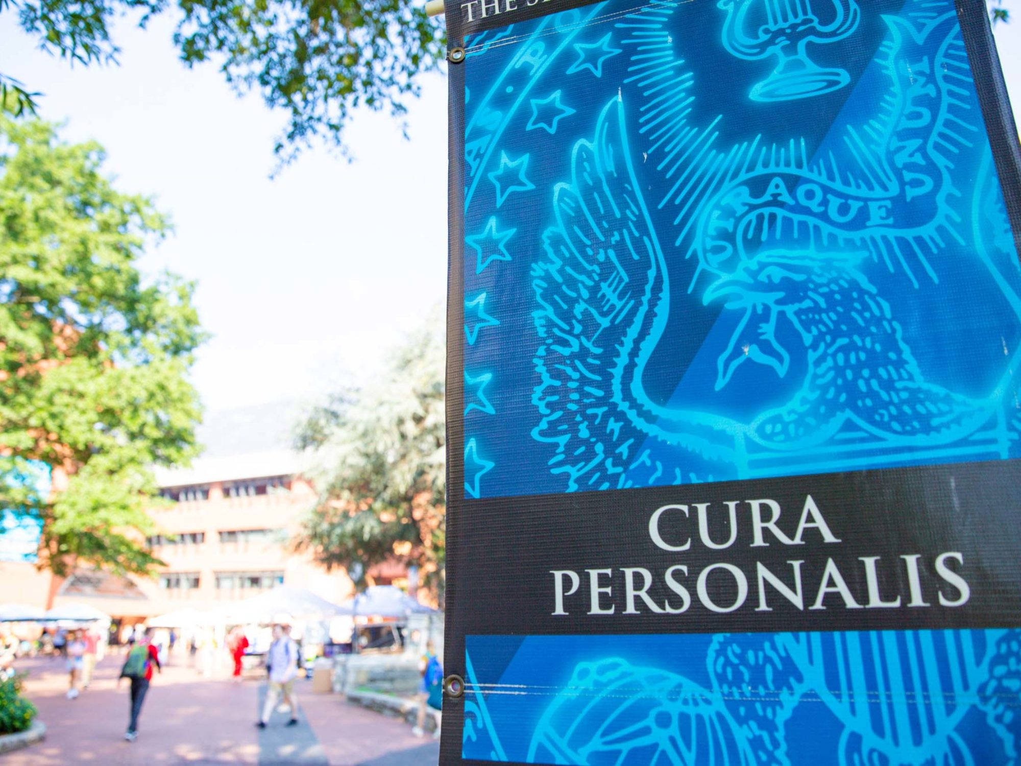 Banner hanging on campus lamppost that reads Cura Personalis
