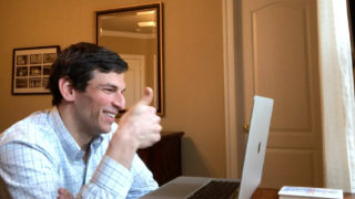 Dr. David Fajgenbaum seated at his laptop giving a thumbs up while participating in a video conference call